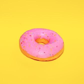 Donut rose sur fond jaune. l'art de la restauration rapide à plat. concept d'amant de beignets