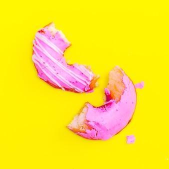 Donut rose sur fond jaune. l'art de la restauration rapide à plat. idée d'amateur de beignets