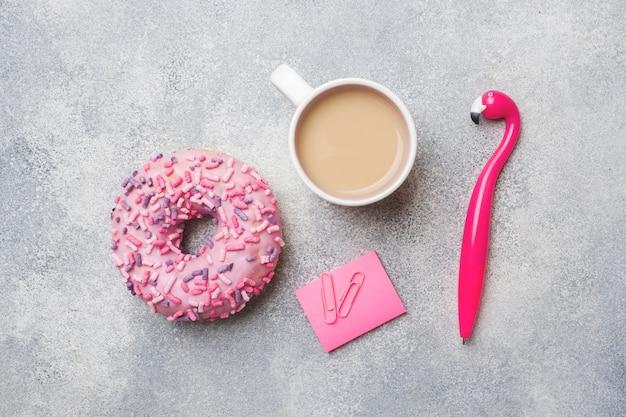 Donut rose et stylo flamingo tasse de café. vue de dessus plat poser.