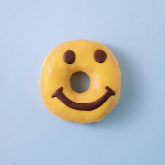 Donut smiley jaune avec glaçage sur fond bleu pastel. concept de nourriture minimale. mise à plat.