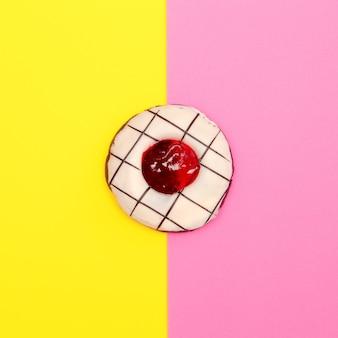 Donut sucré sur un fond coloré. art minimal de restauration rapide à plat