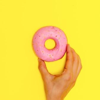 Donut sucré sur fond jaune. l'art de la restauration rapide à plat. concept d'amant de beignets