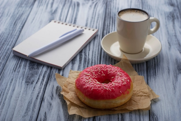 Donut, tasse de café et cahier