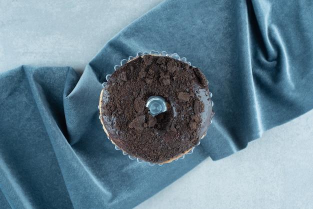 Donut unique sur un petit plateau en verre sur une nappe froissée sur marbre.