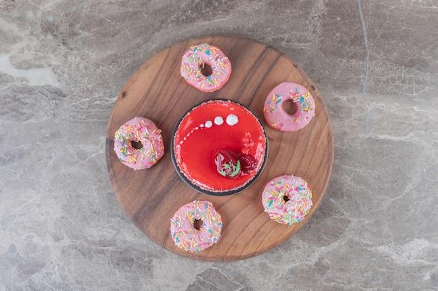 Donuts autour d'un gâteau garni de sirop de fraise sur une planche sur une surface en marbre