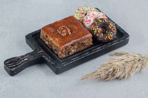 Donuts et un bakhlava sur un petit plateau à côté d'une tige d'herbe de plumes sur fond de marbre.