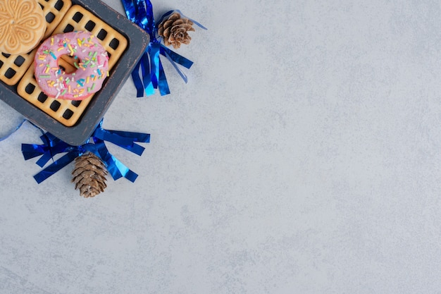 Donuts, biscuits et une marmelade sur un petit plateau au milieu de pommes de pin sur une surface en marbre