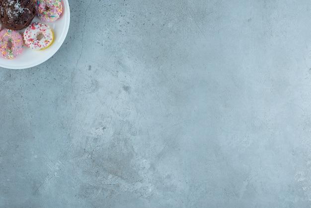 Donuts et un chocolat sur un plateau sur fond de marbre. photo de haute qualité
