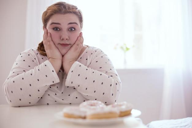 Donuts dans l'assiette. femme potelée perplexe se retenant alors qu'elle était assise à côté d'une délicieuse assiette de beignets