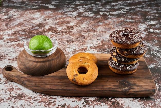 Donuts sur une planche de bois avec du chocolat.