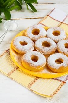 Donuts en poudre de sucre en poudre sur une plaque jaune