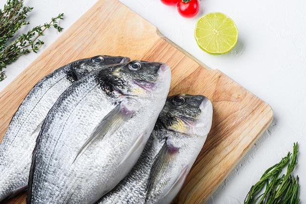 Dorada cru ou poisson daurade sur planche à découper avec des herbes pour grill non cuit sur fond texturé blanc vue latérale.