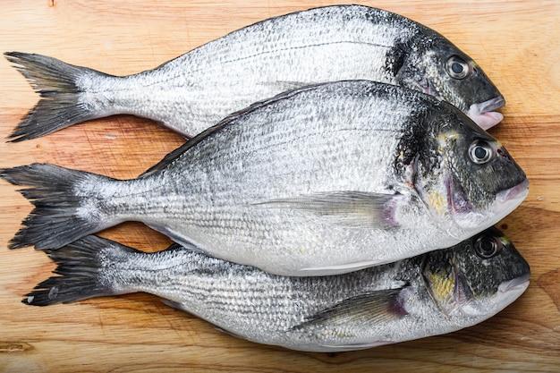 Dorada crue ou poisson daurade sur planche à découper