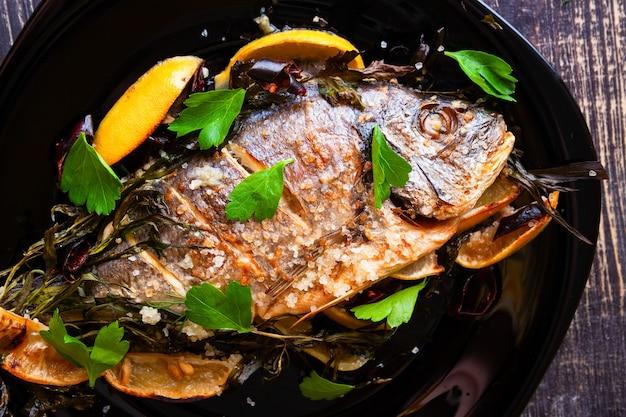 La dorade au four à l'estragon, au persil et au romarin avec du citron frais juteux sur une plaque noire en gros plan