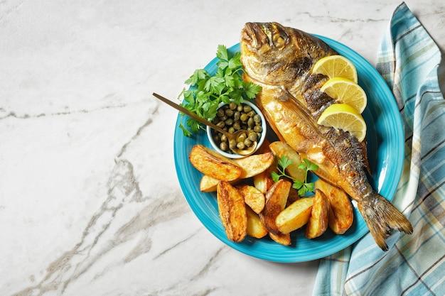Dorade grillée, orata, poisson dorado servi sur une assiette avec pommes de terre rôties et moutarde, vue horizontale d'en haut, mise à plat