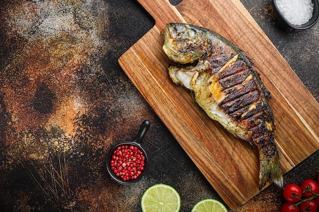 Dorade grillée ou poisson cru dorado sur planche à découper avec des ingrédients sur fond sombre métallisé ancien, vue de dessus avec un espace pour le texte.