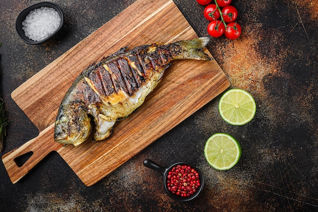 Dorade grillée ou poisson cru dorado sur planche à découper avec des ingrédients sur fond sombre vieux metall, vue de dessus avec un espace pour le texte.