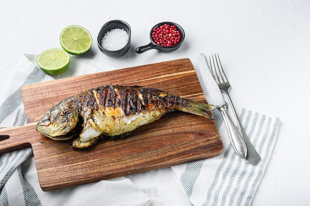 Dorade grillée ou poisson cru dorado sur planche à découper avec des ingrédients sur table blanche texturée, vue latérale.