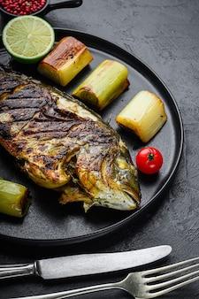 Dorade grillée ou poisson cru dorado sur plaque noire avec poireaux braisés sur fond noir texturé, side view selective focus.