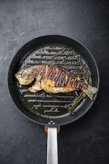 Dorade grillée ou poisson cru dorado sur une poêle chaude grill sur fond noir texturé, vue de dessus.