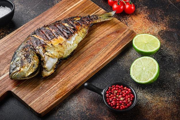 Dorade grillée ou poisson dorado sur planche à découper avec des ingrédients
