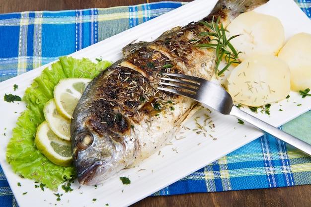 Dorade grillée tête de poisson sur assiette au citron et romarin et