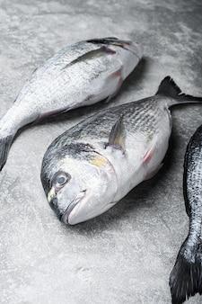 Dorade de poisson entier aux herbes pour griller sur gris texturé