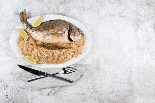 Dorado ou dorade fraîchement grillée au citron et au romarin servie avec du riz. délicieux poisson dorada cuit sur grill dans un restaurant de fruits de mer. la nourriture saine. vue de dessus, espace de copie gratuit.