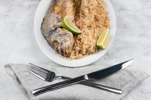 Dorado ou dorade fraîchement grillée au citron et au romarin servie avec du riz. délicieux poisson dorada cuit sur grill dans un restaurant de fruits de mer. la nourriture saine. vue de dessus, espace de copie gratuit