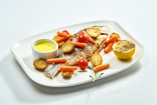 Dorado grillé avec pommes de terre, carottes et tomates cerises dans une assiette blanche. isolé sur une surface blanche. vue d'en-haut