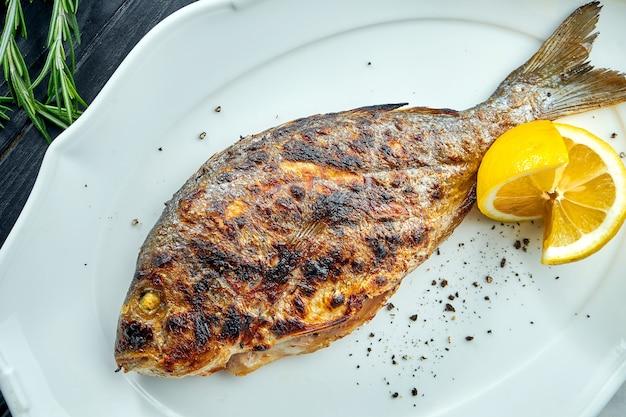 Dorado grillée appétissante sur charbon de bois avec citron, servie dans une assiette blanche sur une surface en bois sombre. barbecue de fruits de mer