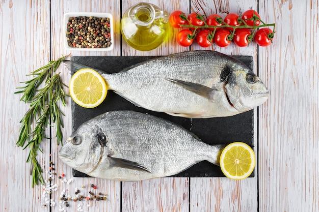 Dorado de poisson cru sur planche à découper en ardoise noire et fond en bois blanc avec épices, tomate, romarin, huile d'olive et citron. vue de dessus, mise à plat avec espace de copie pour le texte