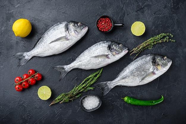 Dorado ou poisson dorade sertie d'herbes pour grill non cuit sur la vue de dessus de table texturée en pierre noire.