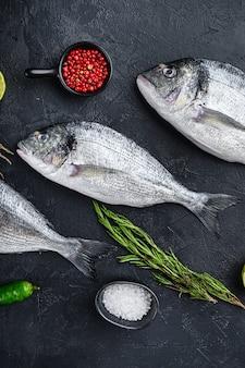 Dorado ou poisson doré aux herbes pour griller non cuit sur la vue de dessus de table texturée en pierre noire.
