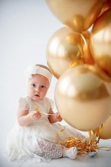 Dorlotez fille, séance, à, a, tas, de, ballons dorés