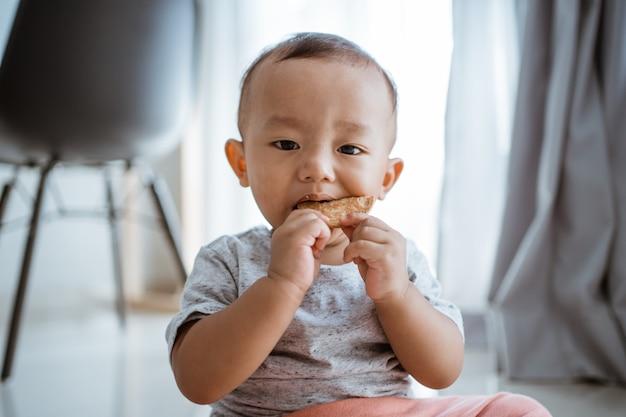 Dorlotez garçon, manger biscuits