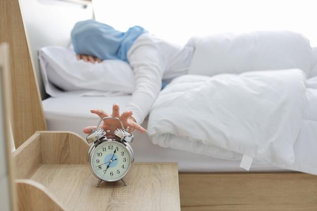 Dormir femme musulmane asiatique portant des vêtements de nuit blancs allongé sur le lit, anneau de réveil manquant se réveiller. vue arrière portrait jeune fille main essayant d'arrêter de sonner tandis que son visage vers le bas sur l'oreiller