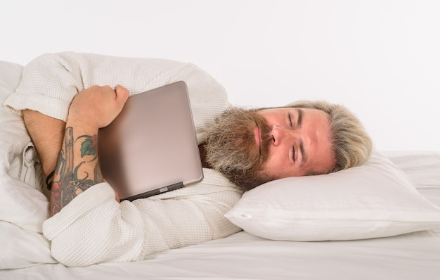 Dormir homme barbu dormir avec un ordinateur portable travailler à domicile homme barbu au lit le matin et réveiller l'homme