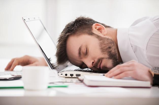 Dormir sur le lieu de travail. jeune homme en tenue de soirée dormant sur le lieu de travail