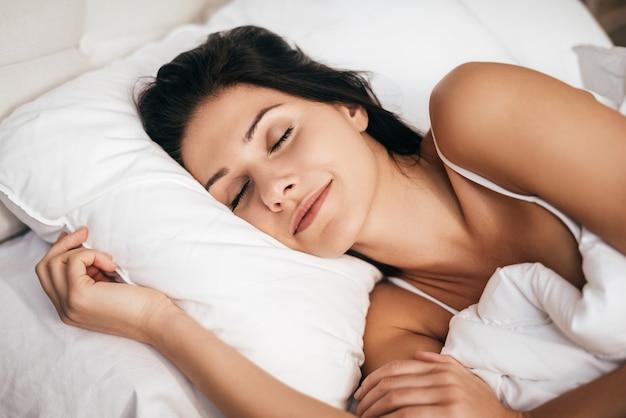 Dormir à la maison. belle jeune femme souriante pendant le sommeil en position couchée dans le lit à la maison
