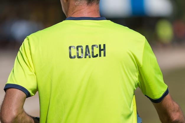 Dos de la chemise de couleur verte brillante d'un entraîneur avec le mot coach écrit sur