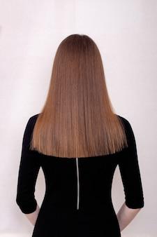 Dos femelle avec de longs cheveux bruns sains et droits dans un salon de coiffure