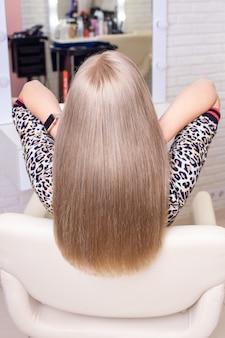 Dos féminin avec de longs cheveux blonds naturels