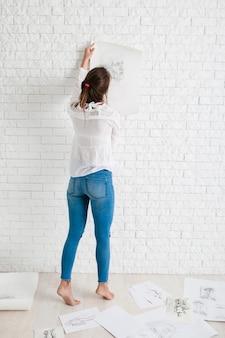 Dos de femme accrochant son croquis sur le mur