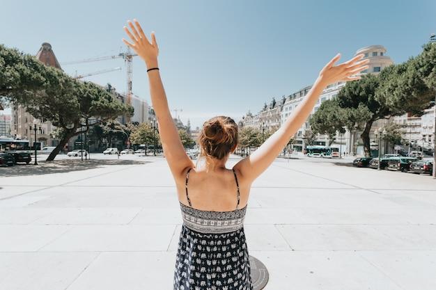 Dos d'une femme célébrant sur la place principale de porto, porto, lors d'une journée très ensoleillée, concept de détente et de vacances, journée chaude, été, robe