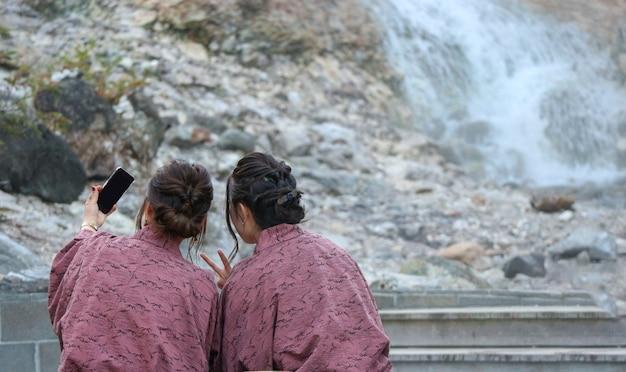 Dos de femmes japonaises qui s'auto-assaillent en se reposant dans un onsen à la ville thermale naturelle
