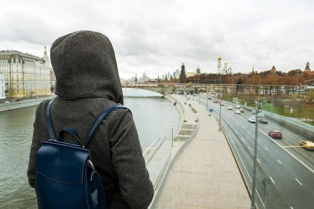 Dos d'une fille avec capuche à la recherche d'une rivière