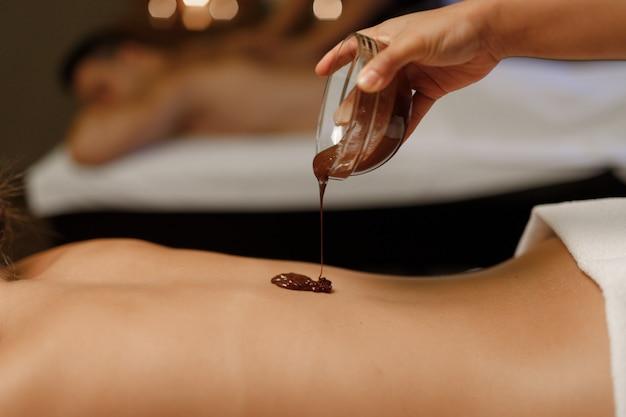 Le dos d'une fille qui reçoit un massage chocolat-balinais