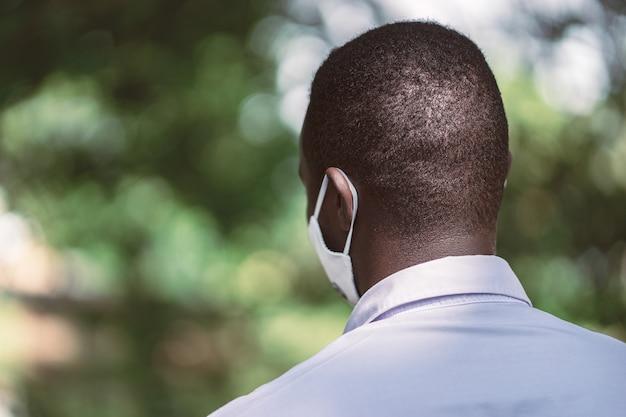 Dos de l'homme africain portant un masque facial