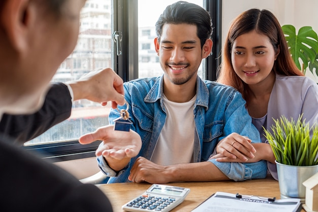 Le dos de la main du représentant des ventes offre le porte-clés à un jeune couple asiatique